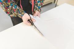 Händerna av sömmerskan klippte saxen på en vit tabell tråd två för sömnad för visare för begrepp för bakgrundsknappcloseup trämör royaltyfria bilder