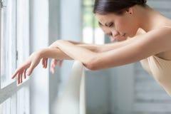 Händerna av två klassiska balettdansörer på barren Arkivbild