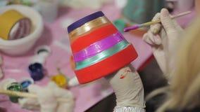Händerna för flicka` s i latexhandskar målar blom- Clay Pot lager videofilmer