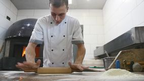 Händerna för kock` s rullar degen in i pizza lager videofilmer