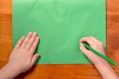Händerna för pojke` s rymmer en grön blyertspenna mot bakgrunden av dokument med olika förslag royaltyfri foto