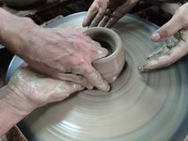 Händerna hugger leran in i den önskade formen r royaltyfria bilder