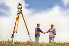 Händeschütteln mit zwei Feldmesseringenieuren auf dem Feld stockfotografie
