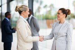 Händeschütteln mit zwei Geschäftsfrauen lizenzfreie stockfotos