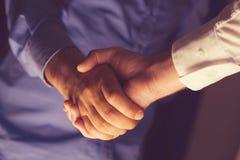 Händeschütteln von zwei Geschäftsleuten Licht von unten Stockfotografie