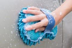 Händewaschen-Brown-Auto mit blauem Schwamm und Blasen schäumen Stockfoto