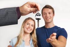Händler-überreichende Schlüssel für Neuwagen zu den jungen Paaren Stockfoto
