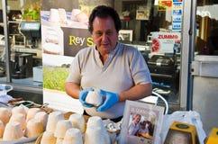Händlerkäse verkaufte den Käse, der in einem weißen Hemd, Hände auf dem Verkäufer zurechtgemacht wurde, der blaue Gummihandschuhe Stockbilder