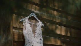 Hänga för bröllopsklänning som är utomhus- den vita bröllopsklänningen som hänger på ett trähus och vinden, svänger klänningen lager videofilmer