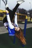Hänga för ung flicka som är uppochnervänt på lekplatsen Fotografering för Bildbyråer