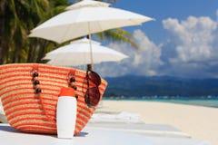 Hänga löst, solexponeringsglas och suncream på den tropiska stranden Royaltyfri Fotografi