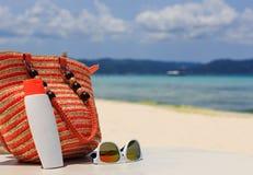 Hänga löst, solexponeringsglas och suncream på den tropiska stranden Arkivbild
