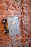 Hänga på en gammal retro telefon för tegelstenvägg royaltyfria foton
