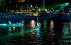 Hängande akrobater precis ovanför vattnet i grön ligth royaltyfri fotografi