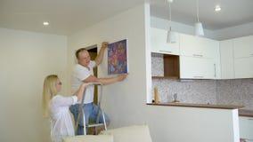 Hängande bild för lyckliga par på väggen hemma Folk, man, kvinna, make, fru, par, hem- dekor och renovering stock video