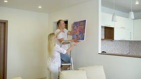Hängande bild för lyckliga par på väggen hemma Folk, man, kvinna, make, fru, par, hem- dekor och renovering arkivfilmer