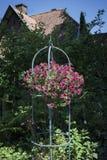 Hängande blommakorg framme av ett hus Royaltyfria Foton