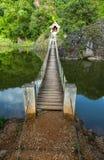 Hängande bro över floden till ön Arkivfoto