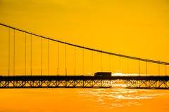 Hängande bro för lastbil korsning på solnedgången Fotografering för Bildbyråer