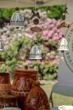 H?ngande delikata handgjorda keramiska klockor och n?gra krukor i bakgrunden royaltyfria bilder