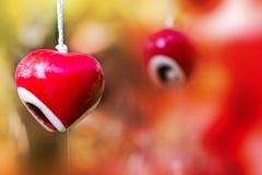 Hängande för valentin` s för röd hjärta keramisk mobil bakgrund för dag Arkivbilder