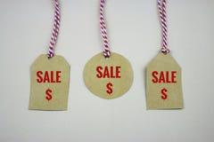 Hängande försäljningsetikettsetiketter på den vita tabellen Fotografering för Bildbyråer