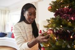 Hängande garneringar för kvinna på julgranen hemma arkivbild