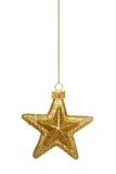 Hängande guld- stjärnajulprydnad över vit royaltyfri fotografi