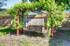 Hängande gunga på den fäktade bakgården med det trevliga landskapet som desing Arkivfoton