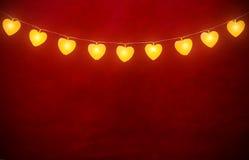 Hängande hjärta tänder på rep med röd bakgrund Fotografering för Bildbyråer