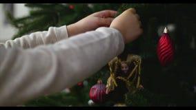 Hängande julprydnader på ett träd med julljus Händer av flickan dekorerar lite en julgran, närbild stock video