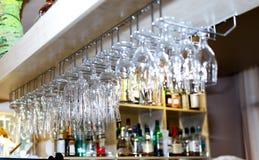 Hängande oj hylla för vinexponeringsglas i bar & restaurang arkivfoto