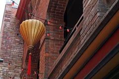 Hängande pappers- lykta och en rad av röda ljus i kineskvarter Arkivbilder