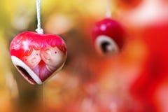Hängande röd keramisk mobil med älskvärda pardockor inom Arkivfoto