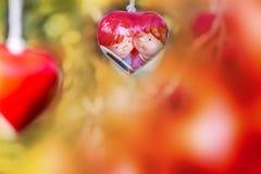 Hängande röd keramisk mobil med älskvärda pardockor inom Royaltyfria Bilder