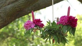 Hängande stearinljus som dekoreras med delikata blommor Att gifta sig aktivering i trädgård, parkerar lager videofilmer