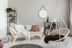 Hängande stol och soffa i ethnovardagsruminre med den runda spegeln Verkligt foto arkivfoto