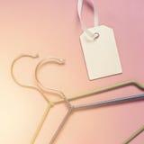Hängare för kläder och etikett på en rosa bakgrund Sale rabatt Arkivbild