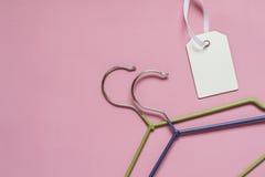 Hängare för kläder och etikett på en rosa bakgrund Sale rabatt, handelbegrepp Royaltyfri Bild