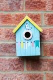 Hängde träfågelhuset för den blåa lilla stickrepliken på tegelstenväggen arkivfoto