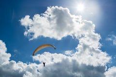 Hängegleiter, der aufwärts reitet, um Wolken unter der Sonne zu erreichen lizenzfreies stockfoto