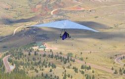 Hängegleiter, der weg von einer Bergspitze am sonnigen Tag schwimmt stockbild