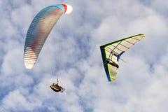 Hängegleiter- und Para-Segelflugzeug kämpfen herein weg auf bewölktem Himmel Stockbild