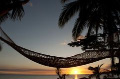 Hängematte auf Strand am Sonnenuntergang in den Fidschi-Inseln Stockfotografie