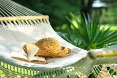 Hängematte, Buch, Hut und Gläser an einem sonnigen Tag Lizenzfreies Stockbild