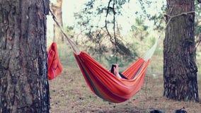 Hängematte entspannen sich Junge Frau, die intelligentes Telefon in der Hängematte am Wald verwendet stock footage