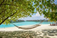 Hängematte am tropischen Strand mit Überwasserbungalows am Hintergrund stockfotografie