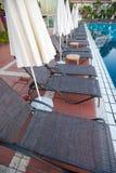 Hängematten mit Regenschirmen durch das Pool für Gäste lizenzfreies stockfoto