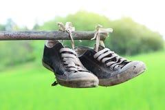 hängen alte stainly Schuhe an der Bambusstange mit grünem Feld Stockbilder