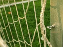 Hängen Sie verbogene Fußballnetze, weißes Fußballfußballnetz Gras auf Fußballspielplatz im Hintergrund Rostfreier Rahmen Lizenzfreies Stockfoto